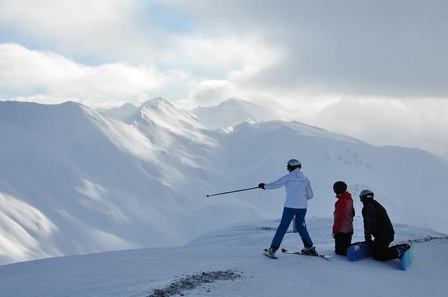 skupinka tří lyžařů v zasněžených horách